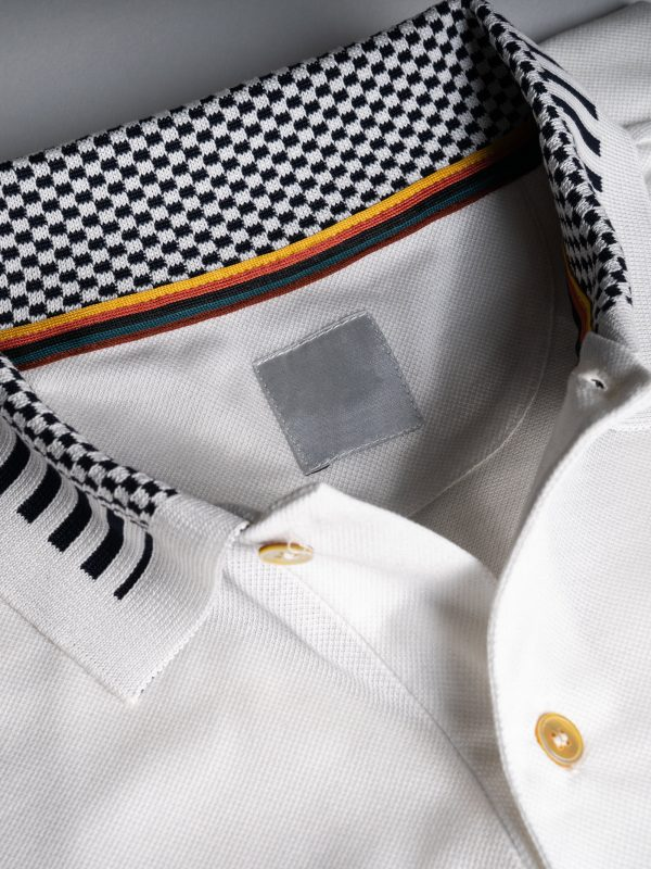 Dettaglio colletto polo da uomo con disegno a scacchi bianchi e neri